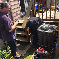 2 ac technicians repairing a centtral air conditioner