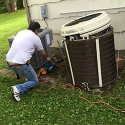 ac technician replacing a central air conditioner